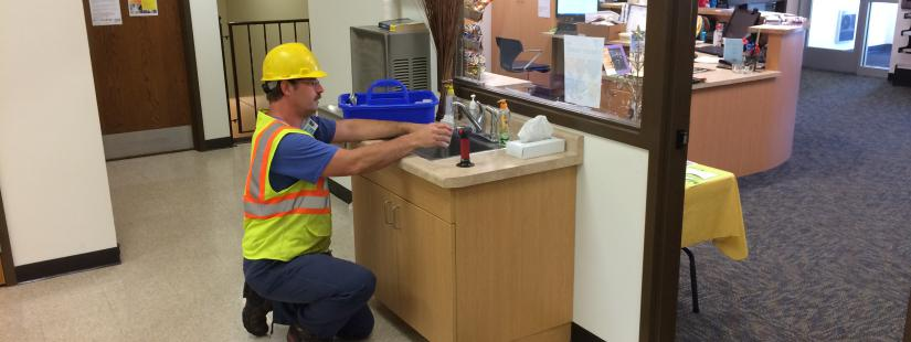 MU employee taking water sample